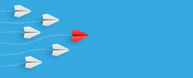 L'aereo di carta rosso individuale guida l'altro