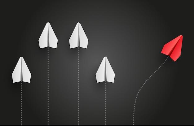 Concetto di individualità. l'aereo di carta rosso leader individuale e unico vola di lato.