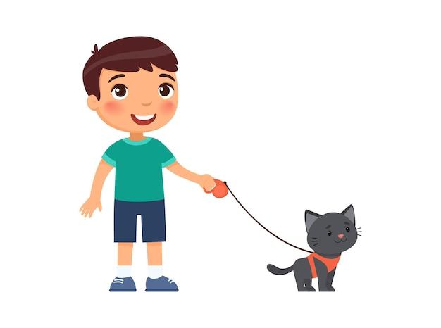Il ragazzino allegro sta tenendo un simpatico gattino nero su un'imbracatura. Vettore Premium