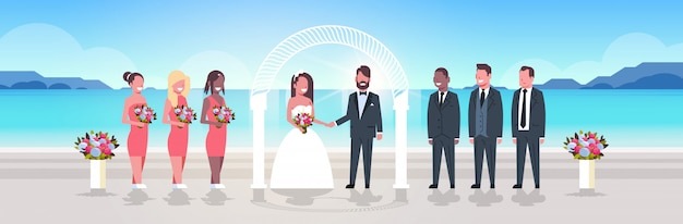 Alba sposi con damigelle groomsmen in piedi insieme sulla spiaggia del mare vicino ad arco cerimonia di nozze concetto alba montagne sfondo a figura intera orizzontale