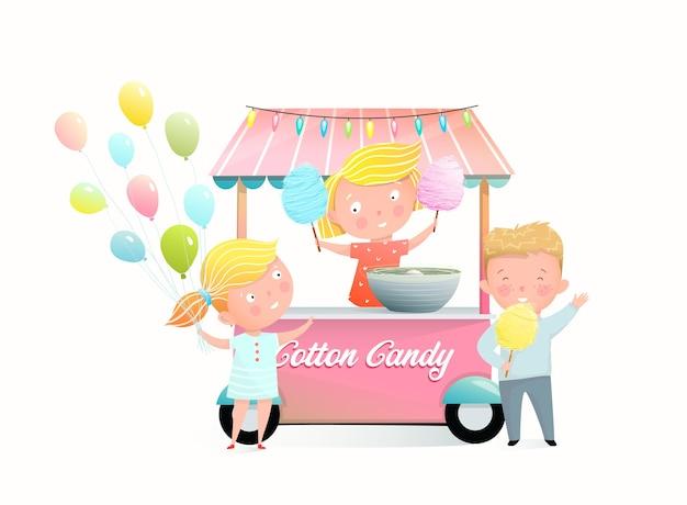 Bambini che comprano zucchero filato alla bancarella della fiera