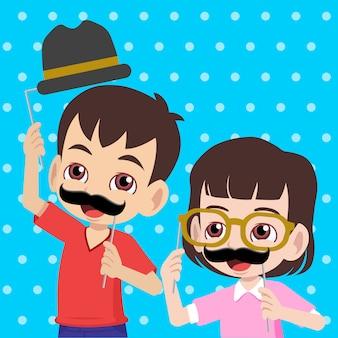 Bambini che si divertono con oggetti di scena di baffi, occhiali e bombetta saluto felice festa del papà