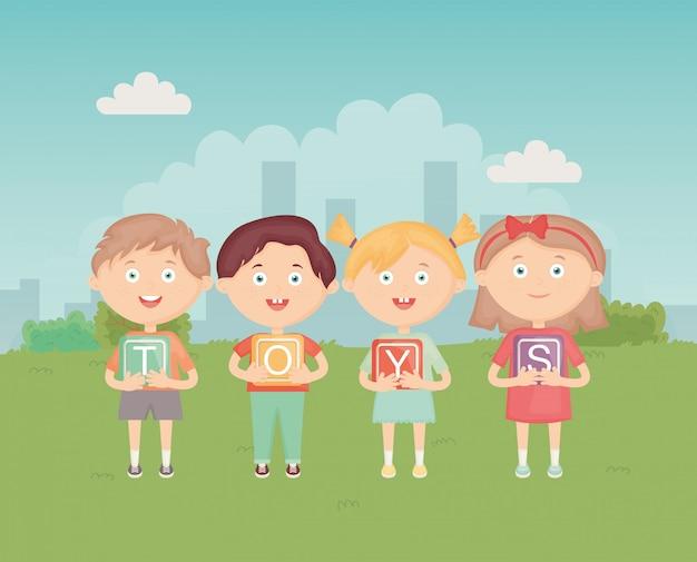 Bambini che tengono i blocchi con l'alfabeto nel parco, giocattoli