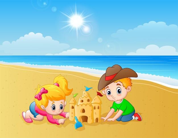 Bambini che fanno il castello di sabbia in spiaggia