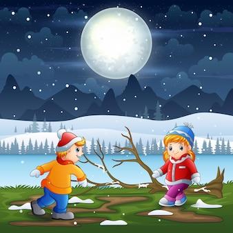 Bambini che giocano nel paesaggio notturno invernale