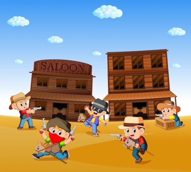 Bambini che indossano il costume da cowboy e giocano con lo sfondo della città occidentale