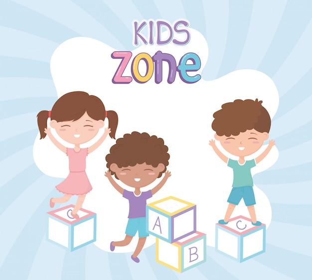 Zona bambini, bambina carina e ragazzi che giocano con i giocattoli di blocchi alfabeto