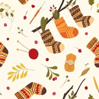 Modello senza cuciture di calzini di lana lavorati a maglia. calde calzature invernali con ornamenti popolari appesi al ramo di un albero. foglie autunnali, rosa canina, bacche di viburno. carta da parati, disegno della carta da imballaggio