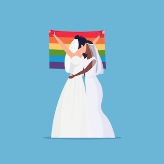 Coppia di spose lesbiche dello stesso genere omosessuale famiglia matrimonio concetto due mix gara ragazze abbracciando tenendo lgbt arcobaleno bandiera femminile personaggi dei cartoni animati a figura intera piatta