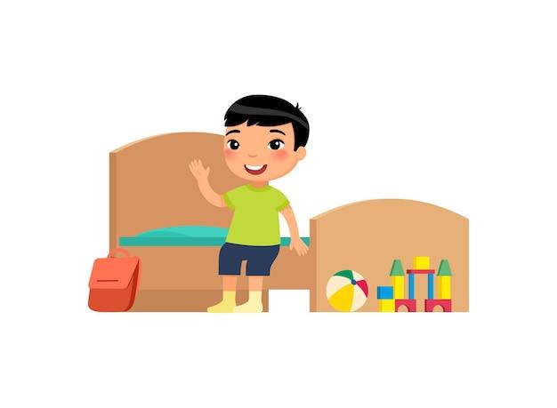 Piccolo ragazzo asiatico nella pulizia e nell'igiene della casa della camera da letto pulita