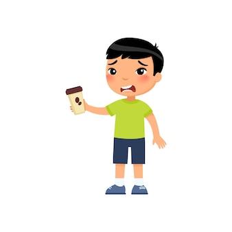 Piccolo ragazzo asiatico con bevanda energetica amara