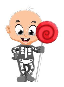 Il piccolo bambino indossa il costume d'osso e tiene in mano il dolce lecca-lecca dell'illustrazione