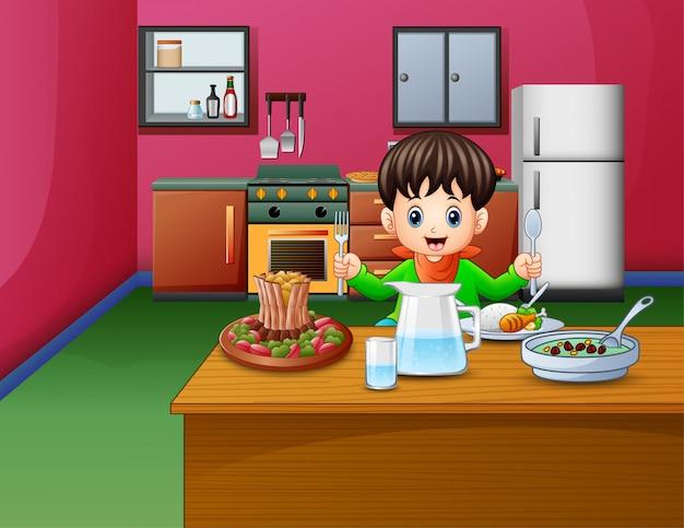 Il ragazzino mangia seduto al tavolo da pranzo
