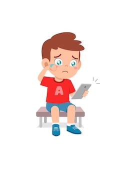 Ragazzino che usa il cellulare e piange