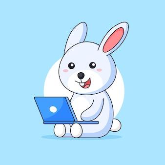 Il piccolo coniglietto si siede e utilizza il computer portatile per mascotte degli animali di lavoro freelance