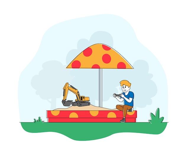 Piccolo bambino che gioca nella sandbox con escavatore giocattolo sul telecomando