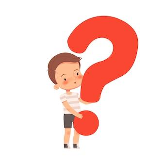 Il piccolo ragazzo curioso sveglio tiene un punto interrogativo. il bambino fa domande ed è interessato al mondo. isolato su sfondo bianco.