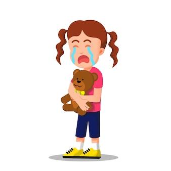 Bambina che piange mentre tiene un orsacchiotto