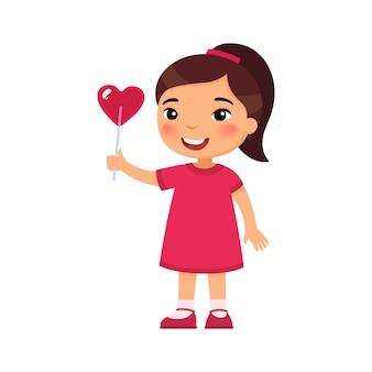 Illustrazione piana di vettore della caramella a forma di cuore della tenuta della bambina