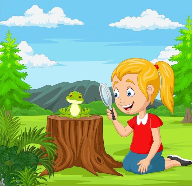 Bambina che esamina rana facendo uso della lente nel giardino