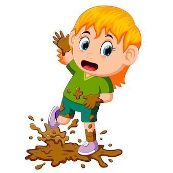 Bambina che gioca nel fango