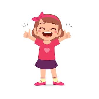 La bambina mostra l'accordo con il pollice sul gesto della mano