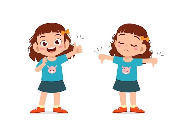 La bambina mostra il pollice di gesto della mano su e il pollice verso il basso