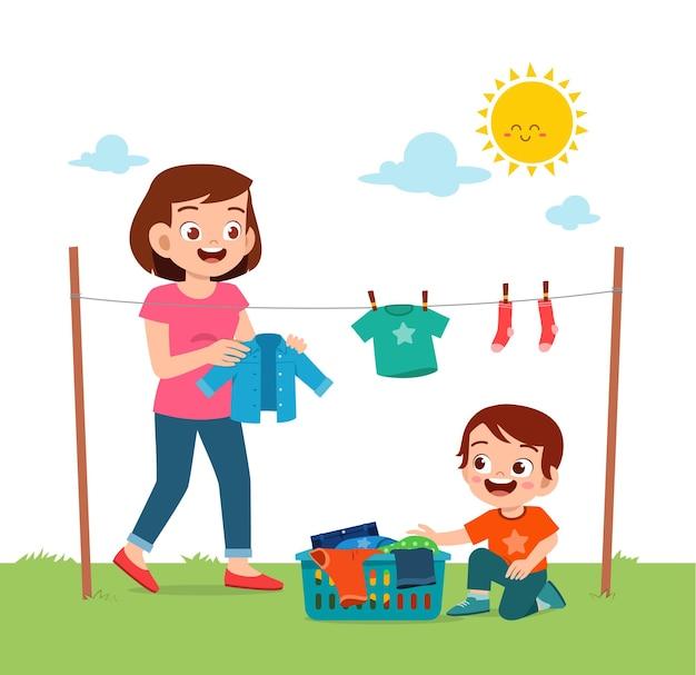 Ragazzino che aiuta la madre ad asciugare i vestiti all'esterno
