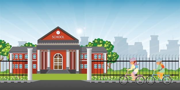 Bambini piccoli che vanno in bicicletta davanti alla scuola.