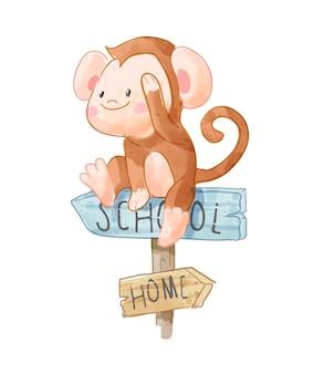 Piccola scimmia che si siede sull'illustrazione del segno di legno della scuola