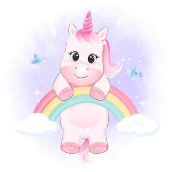 Piccolo unicorno che appende sull'illustrazione dell'acquerello degli uccelli e dell'arcobaleno
