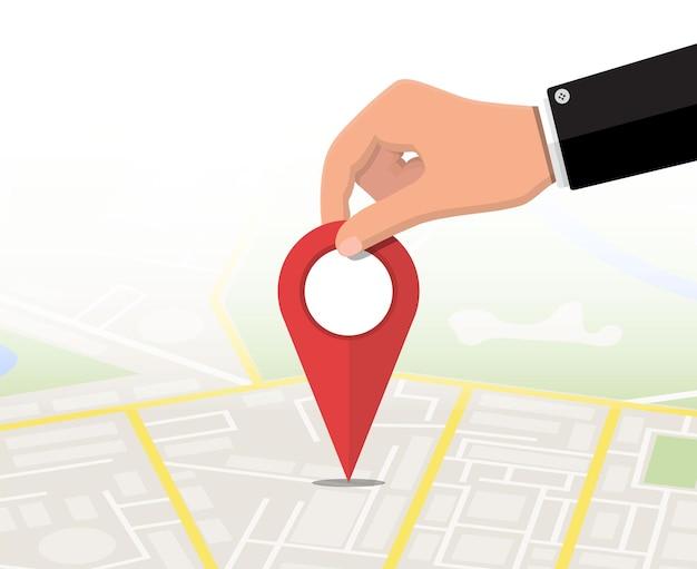 Perno di posizione in mano e mappa. mappa della città con case, parchi, strade e strade. vista aerea della città. gps, navigazione e cartografia. illustrazione vettoriale in stile piatto