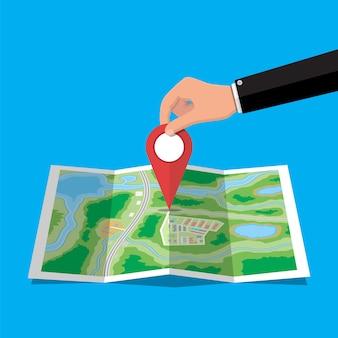 Spilla di posizione in mano e mappa cartacea. mappa della città con case, parchi, strade e strade. vista aerea della città. gps, navigazione e cartografia. illustrazione vettoriale in stile piatto