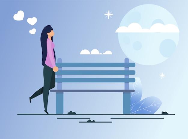 Donna elegante sola che cammina nel parco nella notte