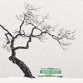 Un albero solitario senza foglie si dirige sopra la panchina verde coperta di neve