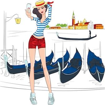 Adorabile ragazza alla moda fa selfie, indossa cappello e camicia a righe come gondoliere su uno sfondo di venezia in stile schizzo
