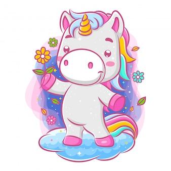 Unicorno adorabile che tiene un fiore e che sta sulla nuvola