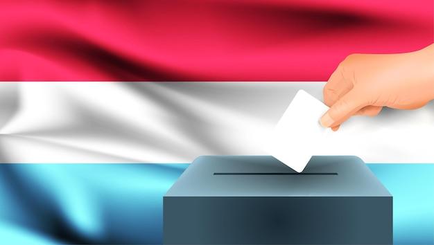 Bandiera del lussemburgo, voto maschio della mano con il fondo di idea di concetto della bandiera del lussemburgo