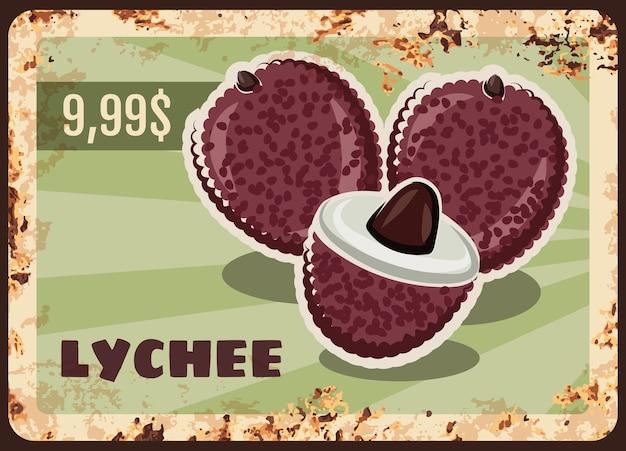 Piastra di metallo arrugginito litchi, segno di latta ruggine vintage con frutta esotica matura intera e metà.