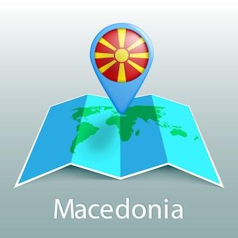 Mappa del mondo di bandiera della macedonia nel pin con il nome del paese su sfondo grigio
