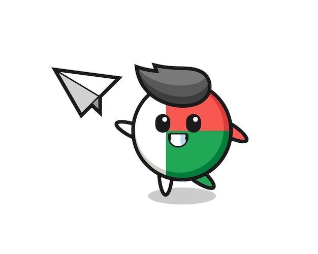 Personaggio dei cartoni animati del distintivo della bandiera del madagascar che lancia aeroplano di carta, design carino