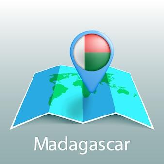 Mappa del mondo di bandiera del madagascar nel pin con il nome del paese su sfondo grigio