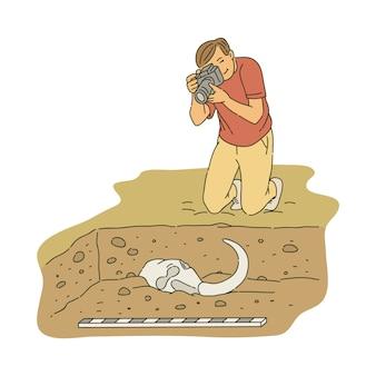Archeologo maschio che si inginocchia e che prende foto di stile antico di schizzo delle ossa