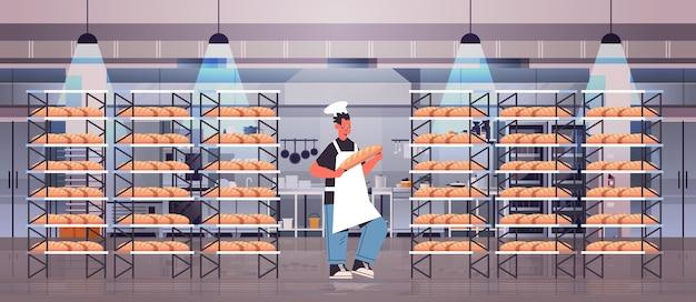 Panettiere maschio in uniforme che tiene il pane prodotti da forno cottura concetto di fabbricazione a figura intera orizzontale illustrazione vettoriale