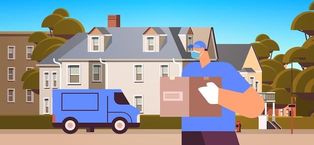 Corriere maschio in maschera e guanti con scatola di cartone consegna senza contatto servizio di corriere medico