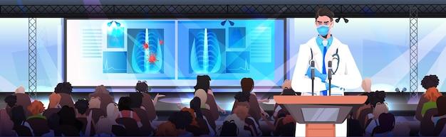 Medico maschio in maschera che dà discorso alla tribuna con microfono lotta contro il concetto di conferenza medica del coronavirus