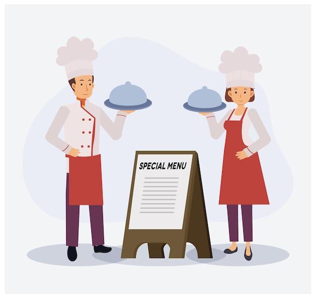 Lo chef maschio e femmina è in piedi e tiene il vassoio del cibo con coperchio vicino al cartello in legno del menu speciale.