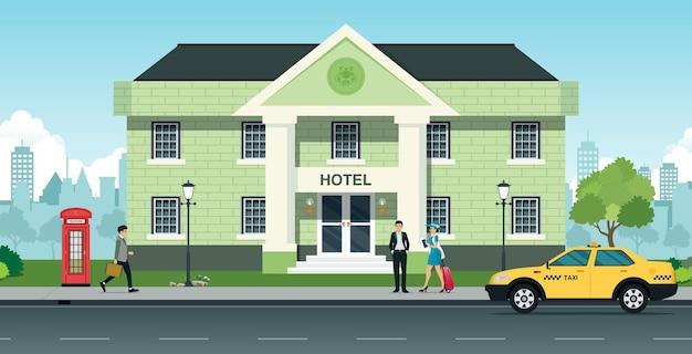 Turiste davanti all'hotel con taxi parcheggiati.