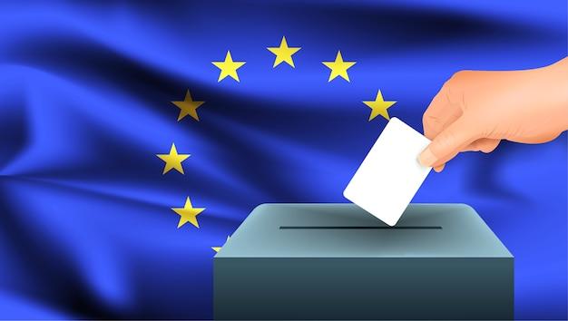 La mano maschio mette giù un foglio di carta bianco con un segno come simbolo di una scheda elettorale sullo sfondo della bandiera dell'unione europea. ue il simbolo delle elezioni