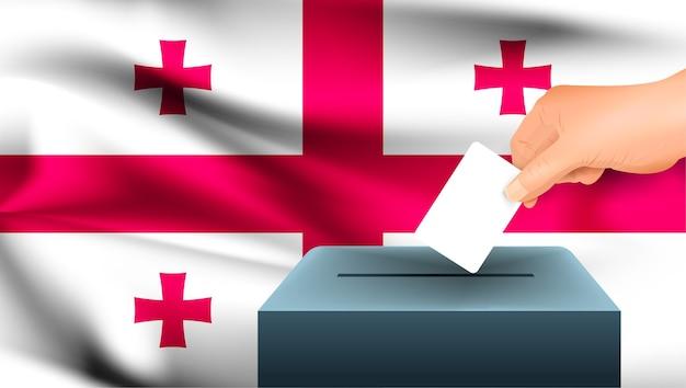 La mano maschio mette giù un foglio di carta bianco con un segno come simbolo di una scheda elettorale sullo sfondo della bandiera della georgia.